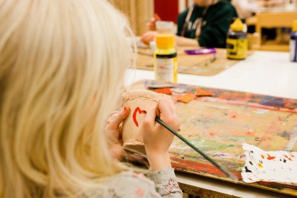 tyttö maalaa kuppia