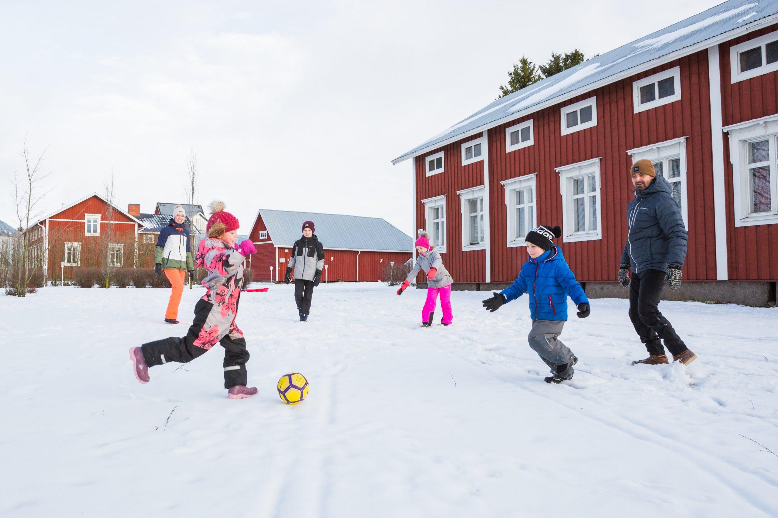 perhe pohjalaistalon edustalla leikkimässä lumella